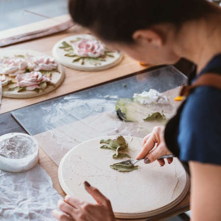 Artist workplace. Inspiration. Ceramic flower artwork in process. Woman with modeling tools working in studio. Stockfoto