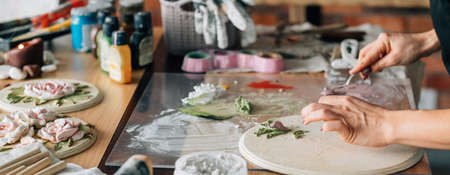 Artist at work. Studio workplace. Ceramic artwork in process. Handicraft. Woman with modeling tools in hand. Imagens