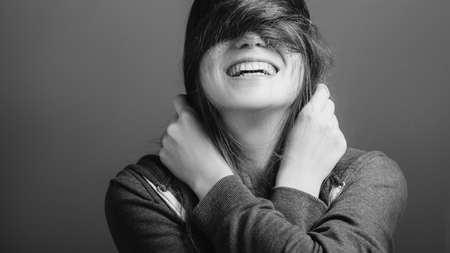 Cheerful mood. Young woman covering eyes with hair. Toothy smile. Black and white portrait. Copy space.