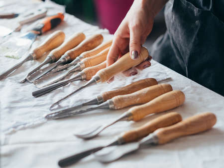 Art craft tools set arranged on table. Carving and modeling equipment. Woman hand choosing chisel. Stock Photo
