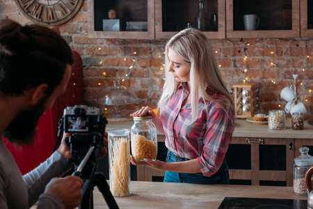 Food blogger. Advice. Female lifestyle. Culinary podcast. Man shooting young woman with jars of pasta. Loft kitchen space. Stock Photo