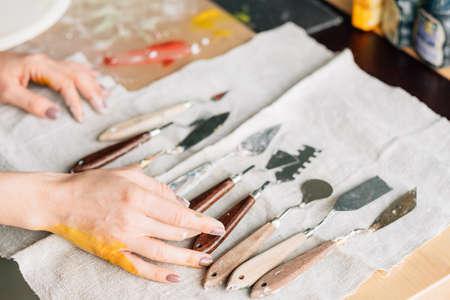Artist supplies. Art craft set composition arranged on ivory textile. Woman hand choosing tool.
