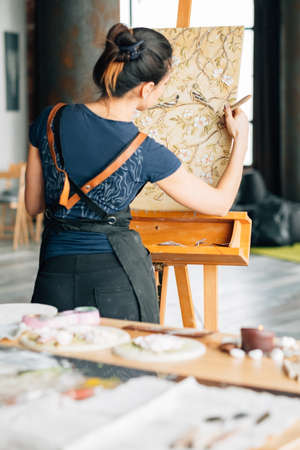 Artist at work. Studio workspace. Woman painter with palette knife. Canvas on easel. Art supplies around.