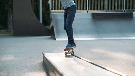 Skateboarding. Man active life. Guy on skateboard in park. Legs in jeans. Copy space.