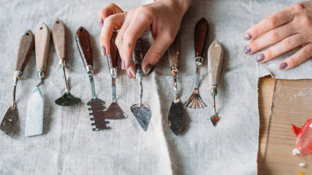 Art craft set arranged on textile. Sculpting and modeling tools. Woman hand choosing palette knife.