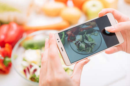 Food blogger taking mobile photo of prepared meal. Online cooking recipes and healthy lifestyle Stock fotó