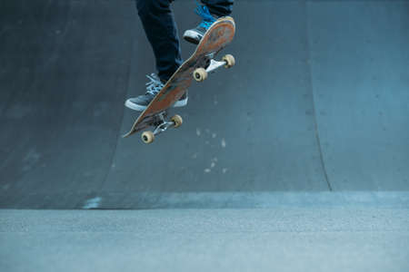 Skateboarder in action. Extreme sports lifestyle. Hipster feet performing ramp trick. Cropped shot. Copy space.
