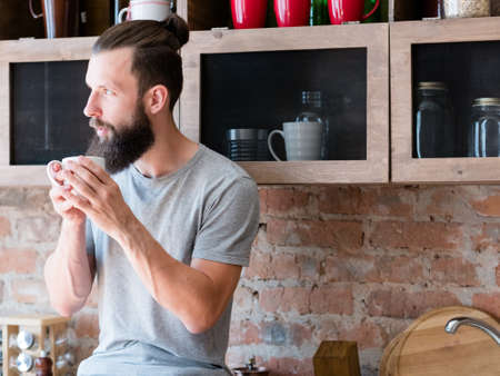 Hot morning drink enjoyment. New day. Rise and shine. Hipster with cup looking sideways thinking. Contemplation.