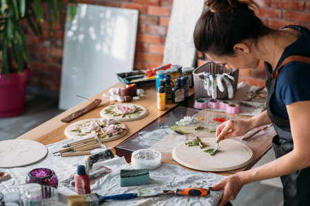 Artist workplace. Inspiration. Ceramic flower artwork in process. Woman with modeling tools working in studio. Imagens