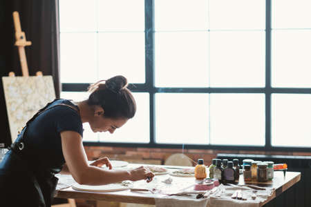 Artist at work. Studio workplace. Ceramic artwork in process. Handicraft. Woman with modeling tools in hands.