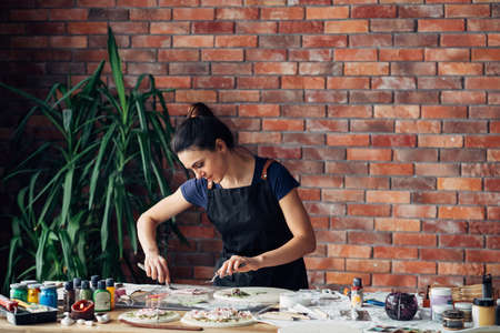 Artist studio. Clay handicraft in process. Young woman with modeling tools variety at workplace. Copy space.