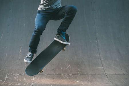 Skateboarder in Aktion. Extremsport-Lifestyle. Hipster, der Ollie-Trick durchführt. Abgeschnittener Schuss. Platz kopieren. Standard-Bild