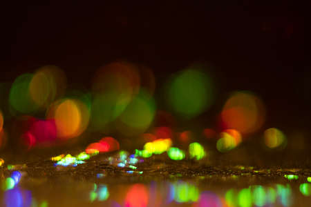 Blurred multicolor bokeh circles on dark background. Defocused lens flare glow. Abstract design. Фото со стока