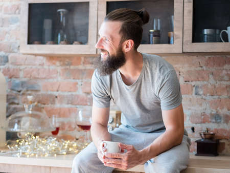 New day. Morning wake up drink. Coffee time. Smiling man with cup sitting on kitchen counter and looking sideways. Stock Photo