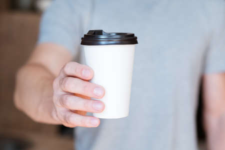 Good morning. Wake up. Energy and vitality drink. Man offering paper coffee cup. Cropped shot. 스톡 콘텐츠