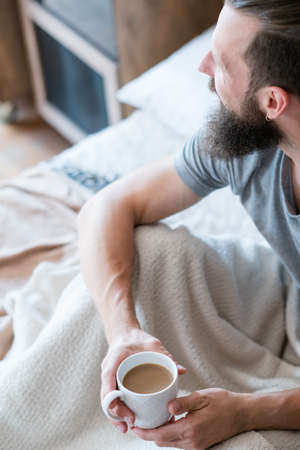 Morning coffee warmth and energy. New day habit. Man in bed looking sideways. Hands around white cup of latte. Stock Photo