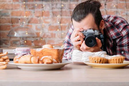 Food photography. Pastry dessert assortment. Man with camera taking photos of plate with meringue. Copy space. Reklamní fotografie