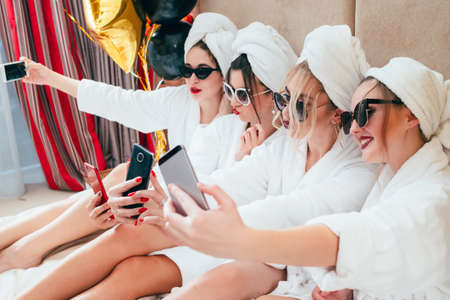 Selfie time. Bathrobe girls taking mobile photography. Fun and relaxation habit. Sunglasses and towel turbans on. Stock fotó - 119753360