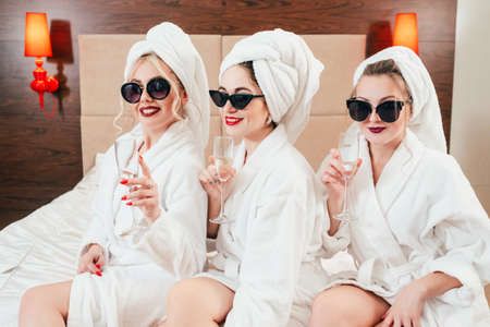 Spa leisure time. BFF relaxation lifestyle. Females with champagne. Sunglasses, bathrobes and towel turbans on.