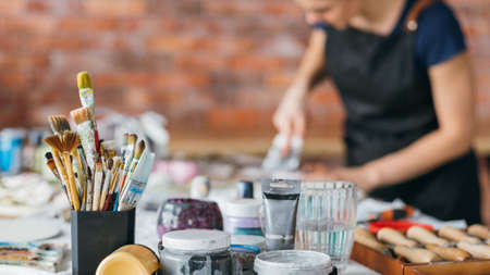 Artist workplace. Brushes, bottles and modeling tools. Art craft. Female in apron working in studio. Inspiration. Фото со стока