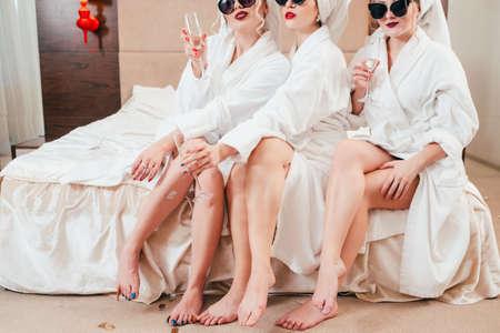 Tiempo de relajación de las mujeres. Hembras arrogantes con champagne. Gafas de sol, albornoces y turbantes puestos. Belleza de piernas desnudas.