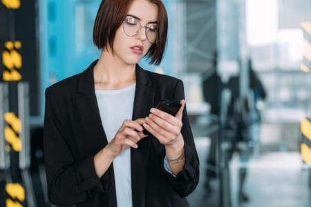 Company leadership. Arrogant beauty. Self assured business woman checking mobile.