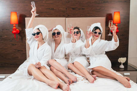 Bachelorette party fun. Smiling females with champagne. Cheers. Sunglasses, bathrobes and turbans on. Bare legs. Reklamní fotografie