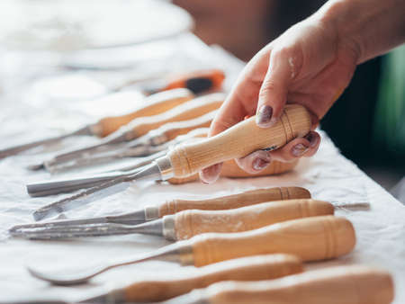 Artist supplies. Art craft set composition arranged on table. Woman hand choosing chisel tool. Stock Photo