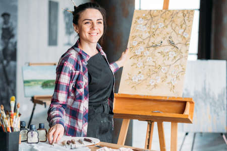Artist inspiration. Dreaming contemplation. Smiling woman painter looking forward. Canvas on easel. Art supplies at workplace.