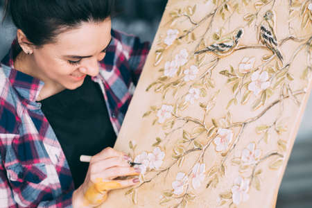 Artist at work. Canvas on easel. Artwork in process. flowers and birds. Smiling woman painter with art tool. Stock Photo