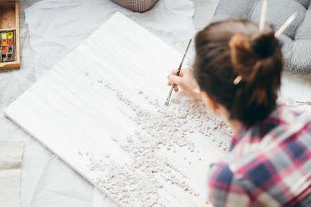 Pittura d'artista. Opera in lavorazione. Concentrazione e ispirazione. Donna con tela sul pavimento. Archivio Fotografico