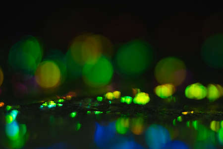 Blurred golden and green bokeh circles on dark background. Defocused lens flare glow.