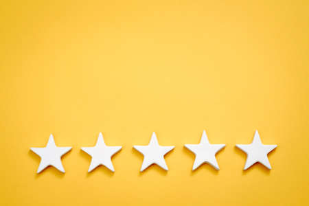 Top quality rating. Evaluation and classification. Five white stars on yellow background. Copy space. 版權商用圖片