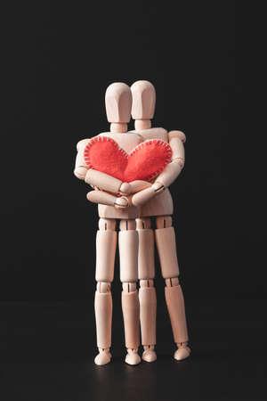 Liebe und Zuneigung. Romantische Beziehung. Sorgfalt und Harmonie. Konzeptionelle gegliederte Mannequin-Komposition. Rotes Herz. Standard-Bild