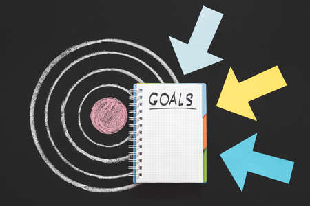 Personal and business goals. Priorities and aims. Aspiration and inspiration. Arrows pointing at notepad on target.