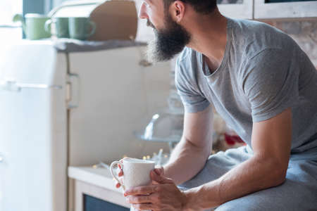 Morning coziness. Home solitude. New day. Man with cup of hot drink sitting on kitchen counter and looking sideways. Stock Photo