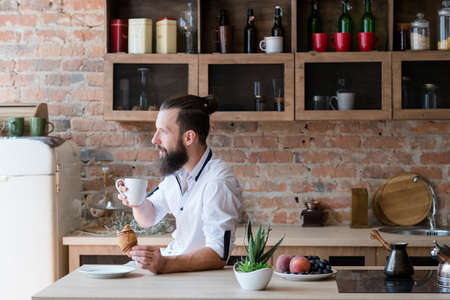 Hipster breakfast. New day. Contemplation. Bearded man with cup of coffee and croissant looking sideways. Loft apartment.