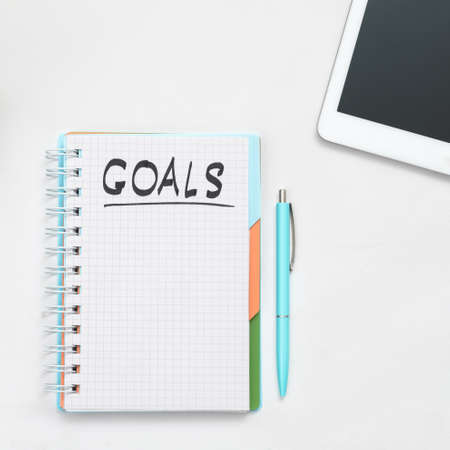 Business goals. Career priorities. Time management. Result to achieve. Notepad mockup. Pen and tablet at hand.