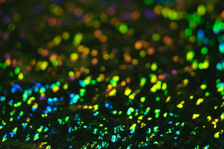 Defocused colorful bokeh circles on dark background. Lens flare illuminated glow. Abstract design.