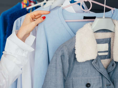 Shopping leisure. Female lifestyle. Woman hand at clothing rack. Selection. Personal style and modern fashion trends.