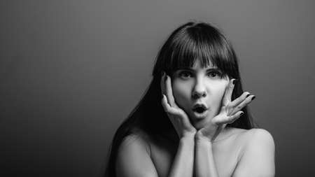 Astonished young woman. Excited facial expression. Black and white closeup portrait of emotional brunette lady.