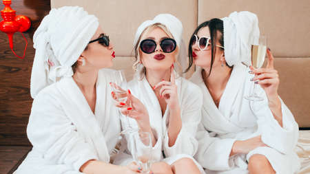Celebration party at spa. Friends congratulation. Young women with champagne. Sunglasses, bathrobes and turbans on. Stockfoto