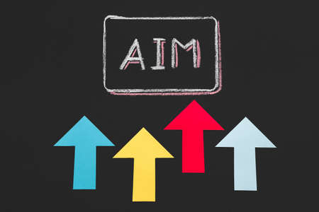 Ambitious attitude. Goal achievement. Motivation and guidance to self development. Colorful arrows pointing at word aim. Stock Photo