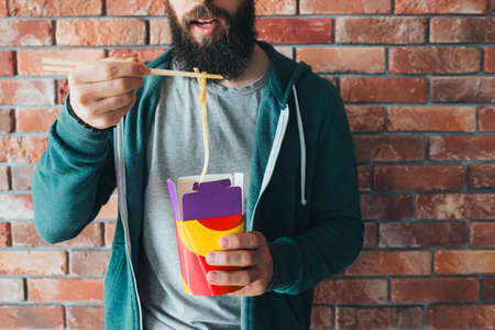 Millennials nutrition. Hipster guy eating chinese noodles with chopsticks. Takeaway lunch meal. Food delivery service.