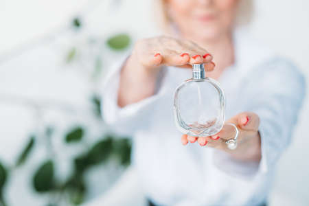 Expensive perfume in woman hand. Elegance and fragrance. Consultant advice on trendy scent. Beauty and luxury.