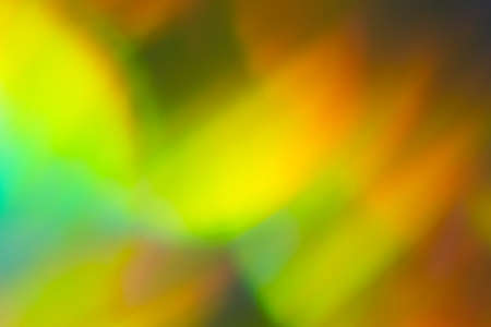 Bokeh abstract background with yellow gleam. Blurry lens flare effect. Colorful lights design.