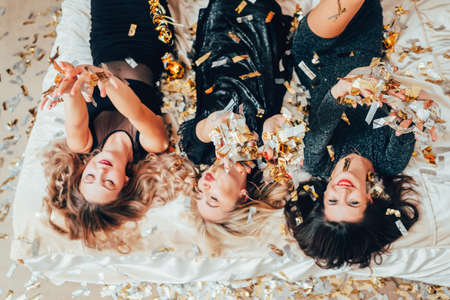 Theme party. Chill out. Group of women in black relaxing on bed under confetti rain. BFF female gathering excitement. Фото со стока