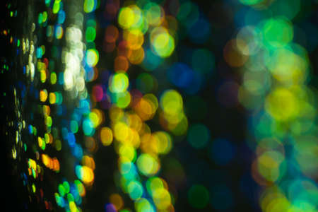 Blurred city night light reflection. Glowing multicolor spots. Bokeh lens flare effect.