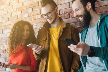 Millennials lifestyle. Young people standing against wall, laughing at fun content on smartphone. Free spirited generation. Stock Photo
