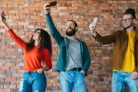 Wealthy millennials obsessed with modern technologies. Young people testing cameras of their latest smartphones. Stock Photo